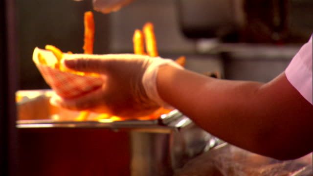 cu unidentifiable hands in plastic gloves placing bacon on commercial grill putting hot dog bacon in bun fast food restaurant preparation obesity... - fleischzange stock-videos und b-roll-filmmaterial