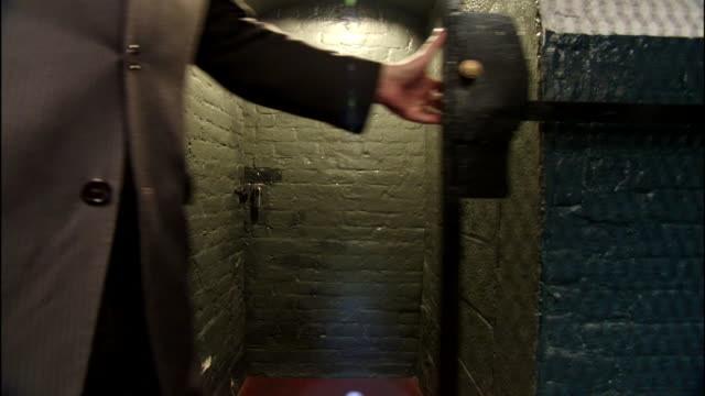 unidentifiable large man/security wearing suit slides open metal grated security gate to stone small room/passage way with concealed brick door.... - grated stock videos & royalty-free footage