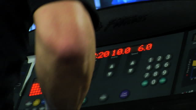 unidentifiable male arm swinging fg, in focus electronic display unit of treadmill console w/ red lights & numbers bg. gym, fitness, machine,... - exercise equipment stock videos & royalty-free footage