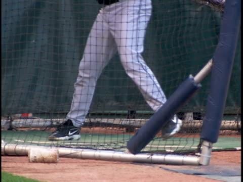 unidentifiable male baseball player wearing black top & gray bottoms in batting cage swinging bat, repeat. sports - gabbia di battuta video stock e b–roll