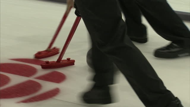 unidentifiable male curlers following sliding curling stone on ice curling sheet, sweeping, stone coming to a stop at center of house. sport, scoring, - slippery stock videos & royalty-free footage