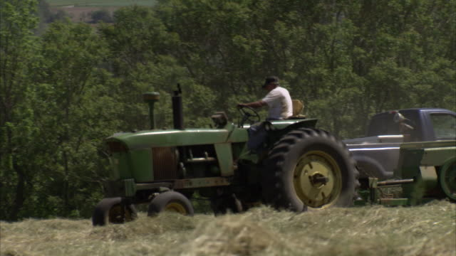 unidentifiable male driving tractor pulling baler baler making hay bales hay bales being launched into larger bale wagon zo to xws of baler... - hay baler stock videos & royalty-free footage