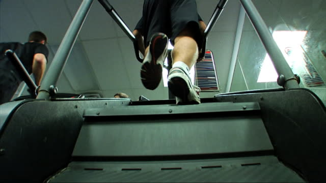 unidentifiable male exercising on stair stepper machine inside unidentifiable fitness facility fg unidentifiable male running on treadmill bg gym... - step video stock e b–roll
