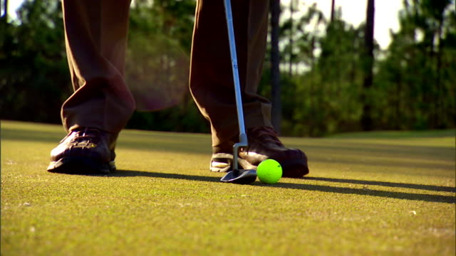 unidentifiable male feet in brown nike golf shoes putter club next to golf ball on green grass male hand in white glove grabbing ball setting on... - golf shoe stock videos & royalty-free footage