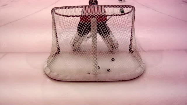 unidentifiable male goalkeeper w/ hockey pads gear crouching low scrambling to protect net on ice rink making multiple saves unidentifiable athletes... - scrambling bildbanksvideor och videomaterial från bakom kulisserna