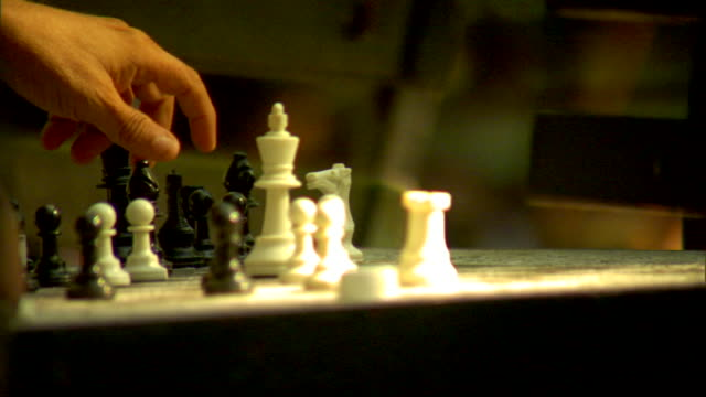 Unidentifiable male hand moving bishop on outdoor chess board table second male hand holding shaking bishop in place OUT