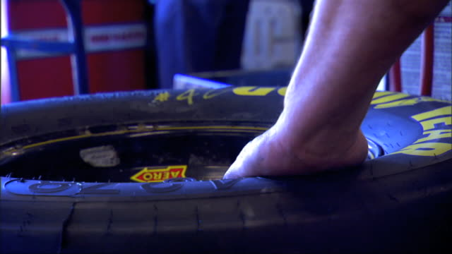 vidéos et rushes de unidentifiable male hand rotating race car wheel w/ race car tire on machine inside garage, hand inserting arm of machine w/ rotating roller into... - mécanicien