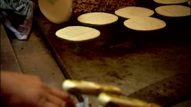 unidentifiable male hand wiping commercial grill w/ blue cloth, meat grilling near multiple small round tortillas, hand flipping tortillas. food,... - tortilla flatbread stock videos & royalty-free footage