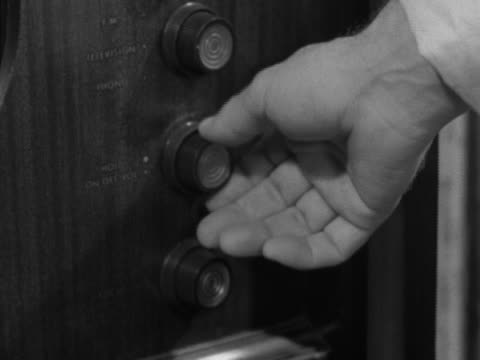 Unidentifiable male hands adjusting knobs on analog television set adjusting 'on/off volume' 'focus' knobs Entertainment black white monochrome TV TV...
