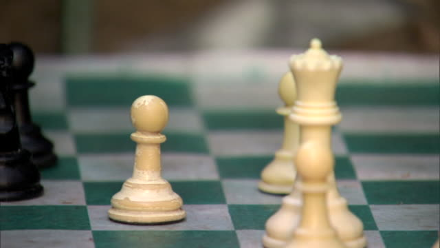 stockvideo's en b-roll-footage met unidentifiable male hands moving chess pieces on chessboard during game outside moving knight pawns eating pawn - schaakstuk