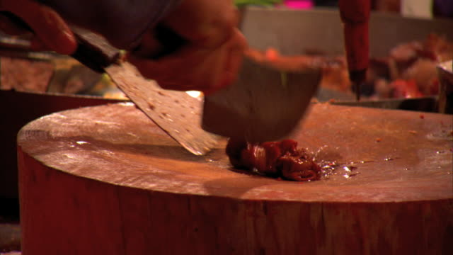 MS Unidentifiable male hands placing tortillas on cooking surface then chopping meat on chopping block w/ cleaver