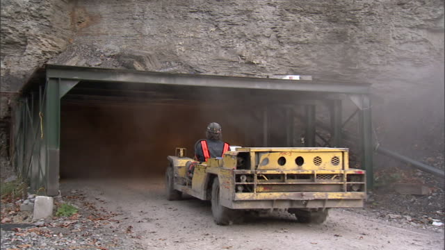 unidentifiable male miner driving low open personnel carrier transporter under scaffold covered rockface mine entrance gray/white smoke working hard... - coal mine stock videos & royalty-free footage