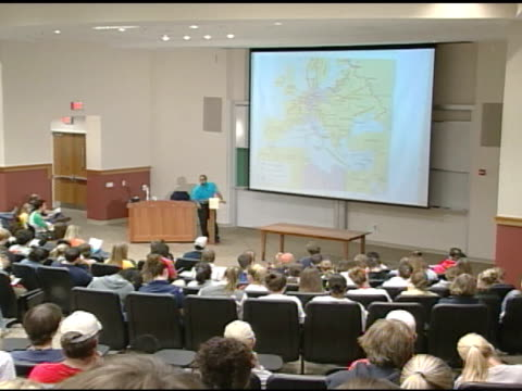 unidentifiable male professor standing in lecture hall stage behind podium talking map of france on projector screen back of students sitting in... - hörsaal stock-videos und b-roll-filmmaterial