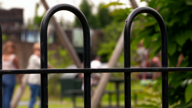 unidentifiable parents and children in playground - railings stock videos & royalty-free footage