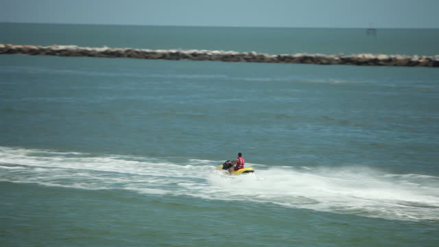 Unidentifiable person riding personal watercraft jet ski across Biscayne Bay moving behind palm trees FG