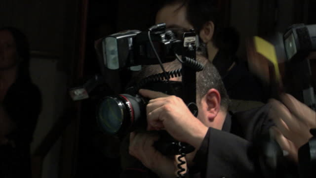 hd mcu unidentifiable photographers adjusting lens and taking pictures along red carpet - kamera blitzlicht stock-videos und b-roll-filmmaterial