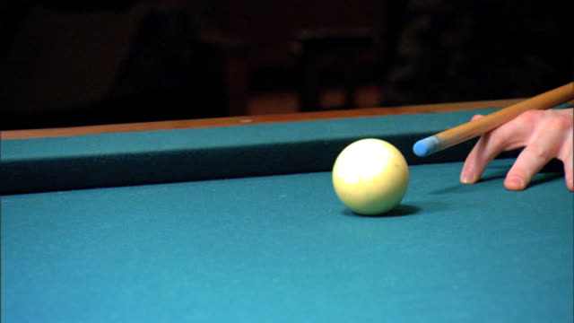 mcu unidentifiable player w/ cue stick striking white cue ball knocking stripe 10 blue ball into side pocket lower frame cue sports cuesports - cue ball stock videos & royalty-free footage