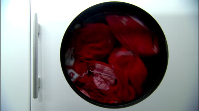 unidentifiable red sports jerseys spinning inside commercial front-load dryer machine. drying, tumbling, tumble, dry, sportswear, electric,... - tumble dryer stock videos & royalty-free footage