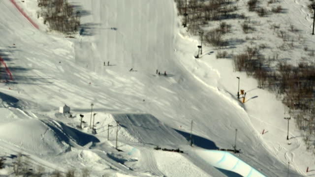 unidentifiable skier skiing down slope on outside of trough, along half-pipe. - halfpipe stock-videos und b-roll-filmmaterial