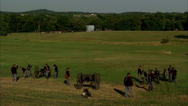 vídeos de stock, filmes e b-roll de unidentifiable union army artillery regiment firing 12pounder napoleon cannons on field smoke confederate state army on field in distance firing bg... - exército da união
