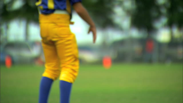 unidentifiable young child boy in football gear on field hitting his thigh pads getting pumped up sports midget league pop warner - jugendmannschaft stock-videos und b-roll-filmmaterial