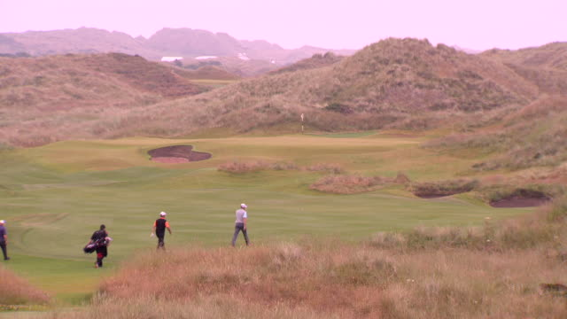 unidentified course green w/ unreadable hole number on flag stick standing in cup w/ marram grass covered dunes bg zo xws golfers amp caddies walking... - links golf stock videos & royalty-free footage