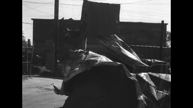 vídeos de stock e filmes b-roll de unidentified crumpled up material lies on ground, building in background / sheet of unidentified material draped over power lines / utility pole with... - amarrotado