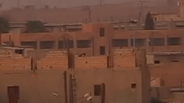 Unidentified distant figures shoot from a rooftop during conflict in Raqqa Syria September 2017 NNBZ127D ABSA627D