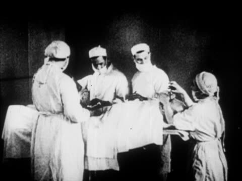 Unidentified doctor being helped into surgical mask working on patient MS Patient w/ partial face bandage VS Red Army Surgeon General MS Womsey...