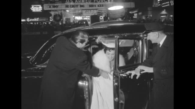 Unidentified female celebrity wearing elaborate hat gets out of limousine at the premiere of The Eddie Cantor Story