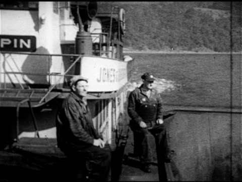 vidéos et rushes de unidentified male sitting w/ tugboat skipper bill cunningham on shannonpin tug deck ws river bank from tug - 1952