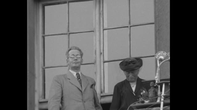 unidentified man and woman stand on balcony with radio microphone nwdr man is emotionally moved by the crowd he sees / large crowd of subdued people... - 1951 bildbanksvideor och videomaterial från bakom kulisserna