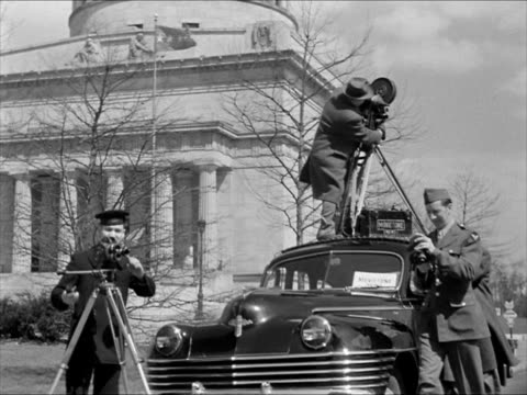 unidentified man w/ motion picture camera tripod on top of car talking to soldiers w/ cameras below ms male turning lens turret on camera us navy... - photographer stock videos & royalty-free footage