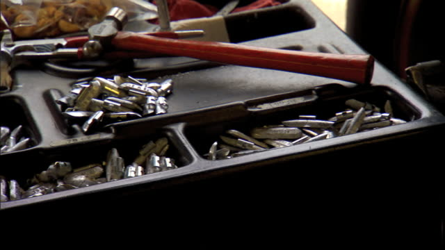 unidentified metal pieces mallet on black tool tray off frame hand placing metal hub nut on tray pan race car tire rolling down pavement in bg... - mallet hand tool stock videos and b-roll footage