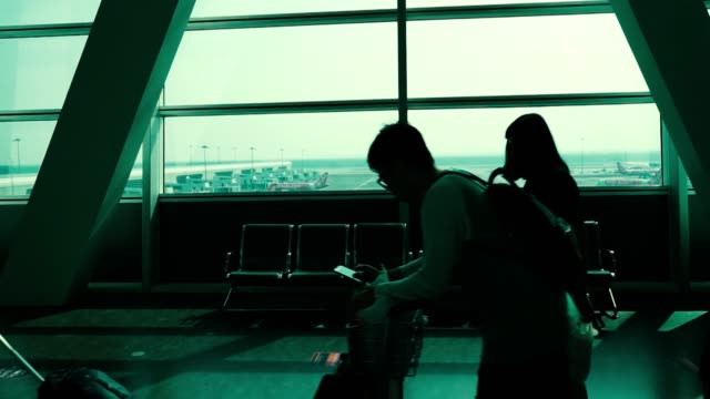 unidentified people are pulling suitcases or carrying backpacks through the airport lounge to reach the boarding gate - flugpassagier stock-videos und b-roll-filmmaterial