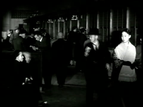 vídeos de stock, filmes e b-roll de unidentified round building int building lobby like bank japanese male in suit standing at desk looking at ticker tape seems very pleased - 1943
