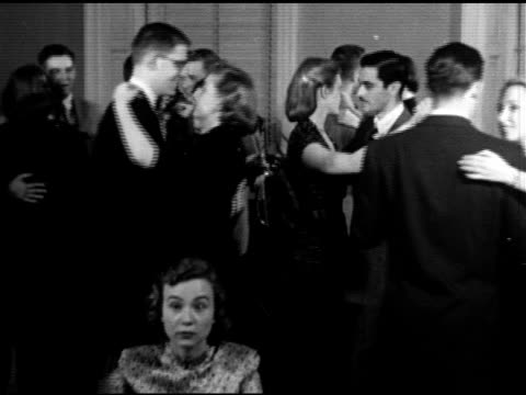 Unidentified students w/ females slow dancing sitting talking socializing in unidentified dormitory residence 'House'