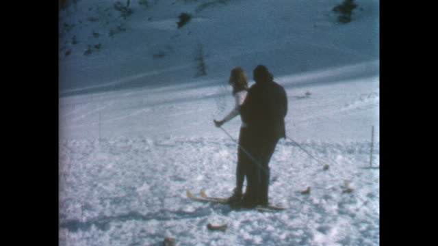 unidentified woman being filmed before she sets off on skis man gets on skis and they ride off together / 8mm amateur home movie footage filmed by... - leo mckern stock videos and b-roll footage