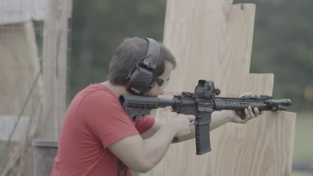 unification church member fires ar-15 at target range, medium shot - pastor stock videos & royalty-free footage