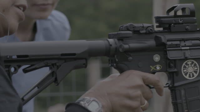 stockvideo's en b-roll-footage met unification church woman cocks and fires ar-15 at target range - bescherming