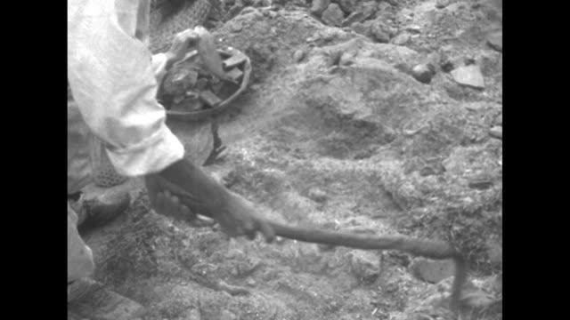 vidéos et rushes de vs uniformed helmeted men with cable and pulley / vs koreans walk through rubble field of devastated town / civilians on street with two women... - actualités cinématographiques