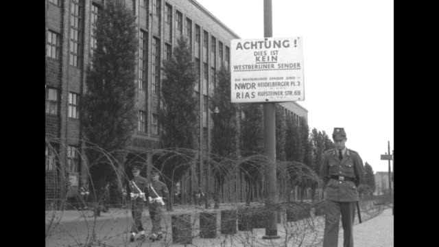 A uniformed man and others on bicycles are seen beyond a barrier of barbed wire / A group of British soldiers in formation adjust their uniforms and...