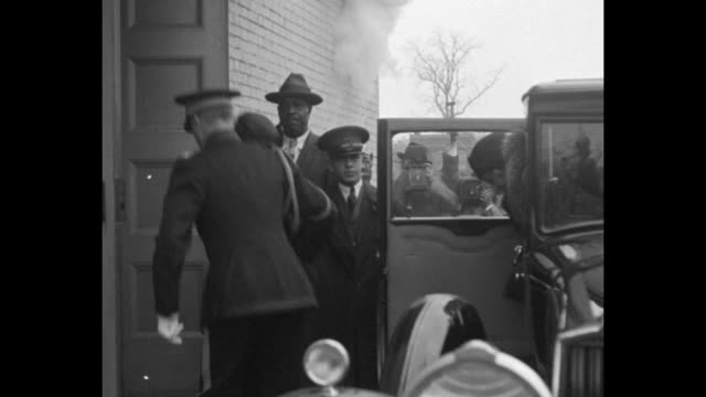 stockvideo's en b-roll-footage met uniformed man helps marie curie alight from car she walks into building followed by another woman a black man stands by building door photographer... - geheime dienstagent