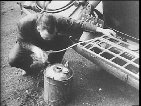 Uniformed man pumping gasoline in to a container / man putting a container in a car trunk / man siphoning gas from a car in to a container / man...