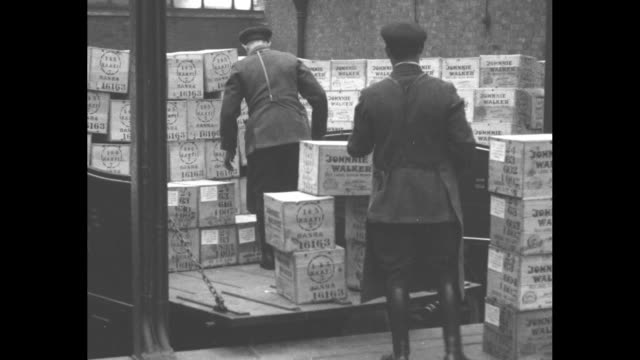 vs uniformed men load a flatbed truck with the wooded crates of liquor the trucks with johnnie walker whisky on the sides offload crates to a waiting... - scotch whiskey stock videos and b-roll footage