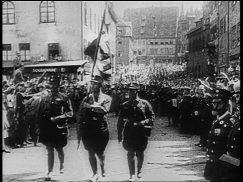 b/w 1929 3 uniformed nazis marching with flags past crowd at rally at nuremberg / newsreel - hakenkreuz stock-videos und b-roll-filmmaterial