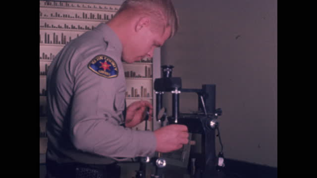 uniformed officer looks through microscope next to bullet case - armed police forces stock videos & royalty-free footage