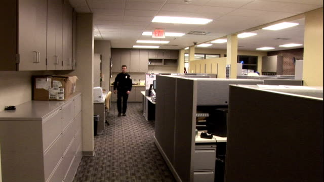 a uniformed police officer walks through an office filled with cubicles and sits at his desk with his computer. - オフィスパーテーション点の映像素材/bロール