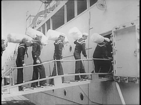 uniformed sailors peruse souvenirs at a table / uniformed sailors write on postcards / a small group of men including uniformed sailors gaze at the... - marinaio video stock e b–roll