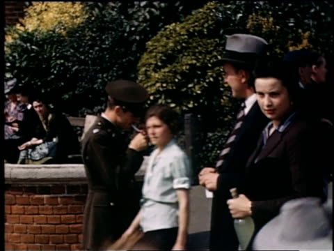 uniformed soldier smoking and walking past pedestrians who are approaching river / london united kingdom - flussufer stock-videos und b-roll-filmmaterial